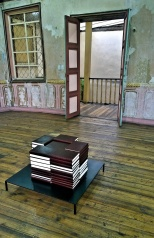 """Daniel Gustav Cramer's """"Ghosts"""": stacked volumes containing 10,000 pages of documented para normal incidents, part of Bienal de Cuenca's """"Leaving to Return""""."""